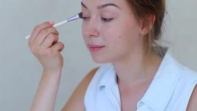 La spazzola compone la mano delle ragazze nella stanza bianca che fa le ombre di trucco video d archivio