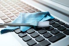 La spazzola e le strofinate puliscono il taccuino sopra messo della tastiera Fotografia Stock