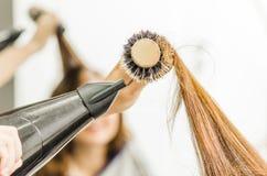 La spazzola per i capelli del primo piano con capelli castana ha turbinato fotografia stock libera da diritti