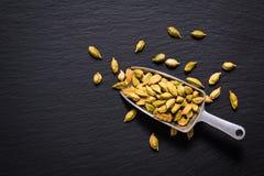 La spezia sana dell'aroma di concetto dell'alimento ha asciugato i cardamomi sull'ardesia nera Fotografia Stock