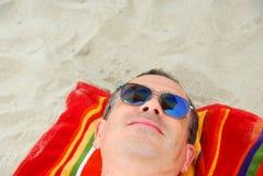 La spiaggia dell'uomo si distende gli occhiali da sole Fotografia Stock