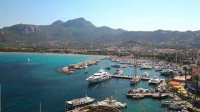 La spiaggia di Calvi e la vecchia città con turchese rimuovono l'acqua dell'oceano in porto con le barche e gli yacht, Corsica, F stock footage