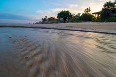 La spiaggia di Hua Hin alla stagione bassa di alte maree dentro durante il tramonto Fotografia Stock