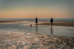 La spiaggia ed il mare ad alta marea nel tramonto nel villaggio olandese del nord di Castricum dal mare nella distanza là AR Immagini Stock
