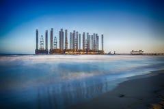La spiaggia ondeggia con la piattaforma petrolifera in mar Caspio Immagine Stock