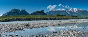 La spiaggia rocciosa sulle banche del Reno con un paesaggio della montagna ha riflesso nella priorità alta Fotografia Stock