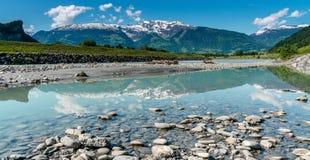 La spiaggia rocciosa sulle banche del Reno con un paesaggio della montagna ha riflesso nella priorità alta Immagine Stock