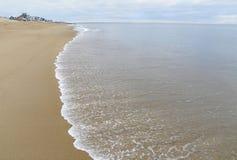 La spiaggia sabbiosa, addolcisce le onde, case nella distanza, vista di oceano Immagine Stock