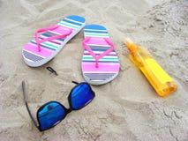 La spiaggia sabbiosa con gli occhiali da sole, i flip-flop e il suncare mungono Fotografie Stock Libere da Diritti