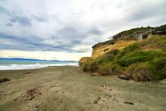 La spiaggia selvaggia della sabbia nera in Catlins con la casa di spiaggia di legno costiera primitiva nella scogliera oscilla, a fotografia stock libera da diritti