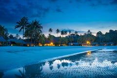 La spiaggia tropicale con le palme e la località di soggiorno si accende alla notte Fotografia Stock