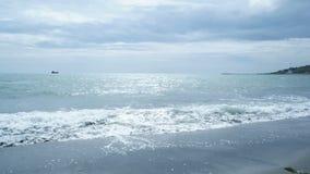 La spiaggia tropicale ondeggia con un cielo nuvoloso archivi video