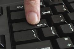 La spinta del dito fornisce la chiave sulla tastiera nera Fotografia Stock