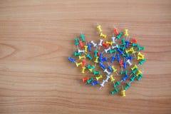 La spinta variopinta di colore appunta le puntine da disegno Vista superiore sulla tavola di legno fotografia stock