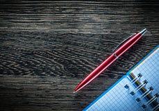 La spirale della penna del biro ha controllato il taccuino sul bordo di legno d'annata Fotografie Stock Libere da Diritti