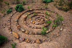 La spirale en pierre a composé d'un bon nombre de différentes roches sur un plancher pierreux sec photo stock