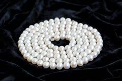 La spirale s'est chargée du collier de perle naturelle sur un velours noir Image libre de droits