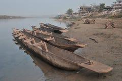 La sponda del fiume con le canoe di legno lunghe nella priorità alta, nei precedenti il villaggio, nella chiara acqua del fiume,  Immagine Stock