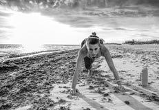 La sportiva attiva negli sport innesta sull'allenamento della spiaggia Fotografie Stock