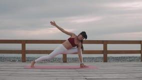 La sportiva fa l'yoga sulla spiaggia tropicale video d archivio