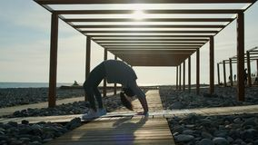 La sportive fait l'exercice de chakrasana en plage, se tenant sur la jambe banque de vidéos