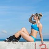 La sportive s'asseyant avec la main sur le front aiment un pare-soleil Photographie stock