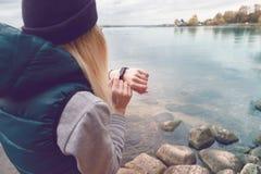La sportive utilise un bracelet-podomètre électronique se tenant sur le rivage de lac Voyage et concept sain de mode de vie dos Photos stock