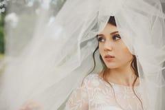 La sposa abbastanza giovane distoglie lo sguardo stante nascosta sotto un velo Immagine Stock