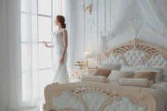 La sposa alla finestra aspetta lo sposo fotografia stock