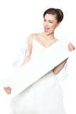 La sposa allegra e felice mostra un manifesto in bianco Fotografia Stock