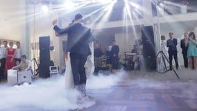 La sposa attraente e lo sposo bello stanno ballando il loro primo ballo nel corridoio di lusso del ristorante archivi video