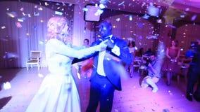 La sposa bionda attraente e lo sposo africano bello stanno ballando felicemente nei coriandoli nel ristorante video d archivio
