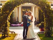 la sposa bionda con un mazzo dei fiori in sue mani ed il suo fidanzato stanno stando vicino ad un arco naturale fotografia stock