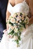 La sposa con i colori di una mano di una rosa Immagine Stock