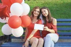 La sposa con la sua amica che si siede nel parco Tenga i palloni fotografia stock libera da diritti