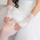 La sposa corregge la giarrettiera sulla sua gamba Immagini Stock