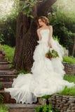La sposa della donna in un vestito da sposa si rilassa facendo una pausa un grande albero Fotografia Stock Libera da Diritti