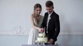 La sposa di bellezza e lo sposo bello stanno tagliando una torta nunziale archivi video