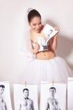 La sposa di divertimento ha rotto una foto che mostra lo sposo Fotografie Stock