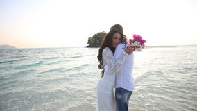 la sposa e lo sposo abbracciano in acqua allo sputo contro l'isola archivi video