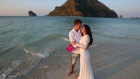 la sposa e lo sposo abbracciano la condizione in acqua contro l'isola stock footage