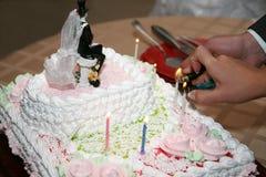 La sposa e lo sposo accendono le candele su una torta nunziale Fotografia Stock