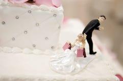 La sposa e lo sposo agglutinano i cappelli a cilindro su una torta nunziale Fotografia Stock Libera da Diritti