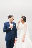 La sposa e lo sposo allegati al fronte incartano i baffi, corona Fotografie Stock
