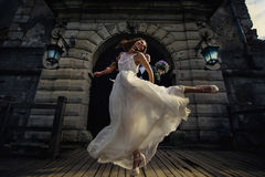 La sposa e lo sposo allegri saltano felicemente nell'aria nella parte anteriore dell' Immagini Stock Libere da Diritti