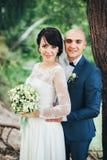 La sposa e lo sposo che abbracciano nella foresta Fotografia Stock