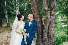 La sposa e lo sposo che abbracciano vicino ad un albero Fotografie Stock Libere da Diritti