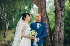 La sposa e lo sposo che abbracciano vicino ad un albero Immagine Stock