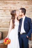 La sposa e lo sposo che baciano sopra wodden il fondo Fotografia Stock