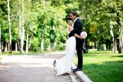La sposa e lo sposo che camminano in estate parcheggiano Fotografia Stock Libera da Diritti